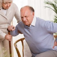 Woman helping an elderly man having a back pain